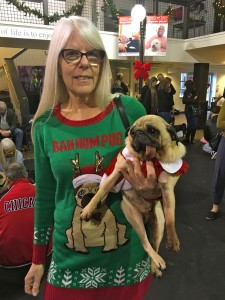 Woman holds her tongue out pug at the Pugalug Pug Claus Christmas Party